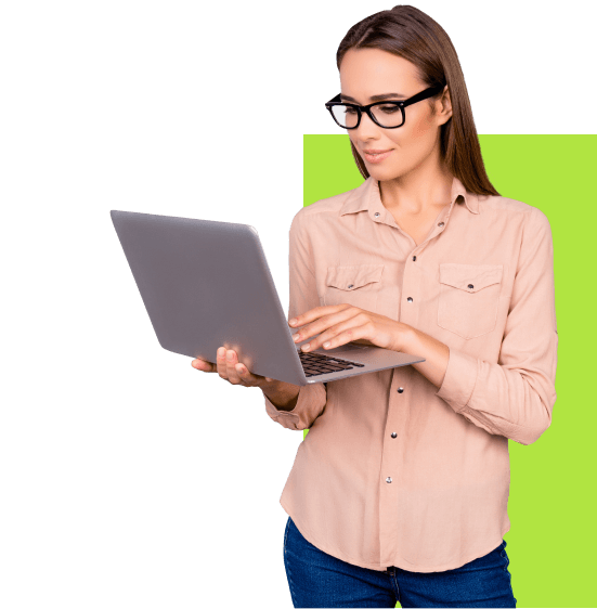 Девушка в очках стоит с ноутбуком в руках